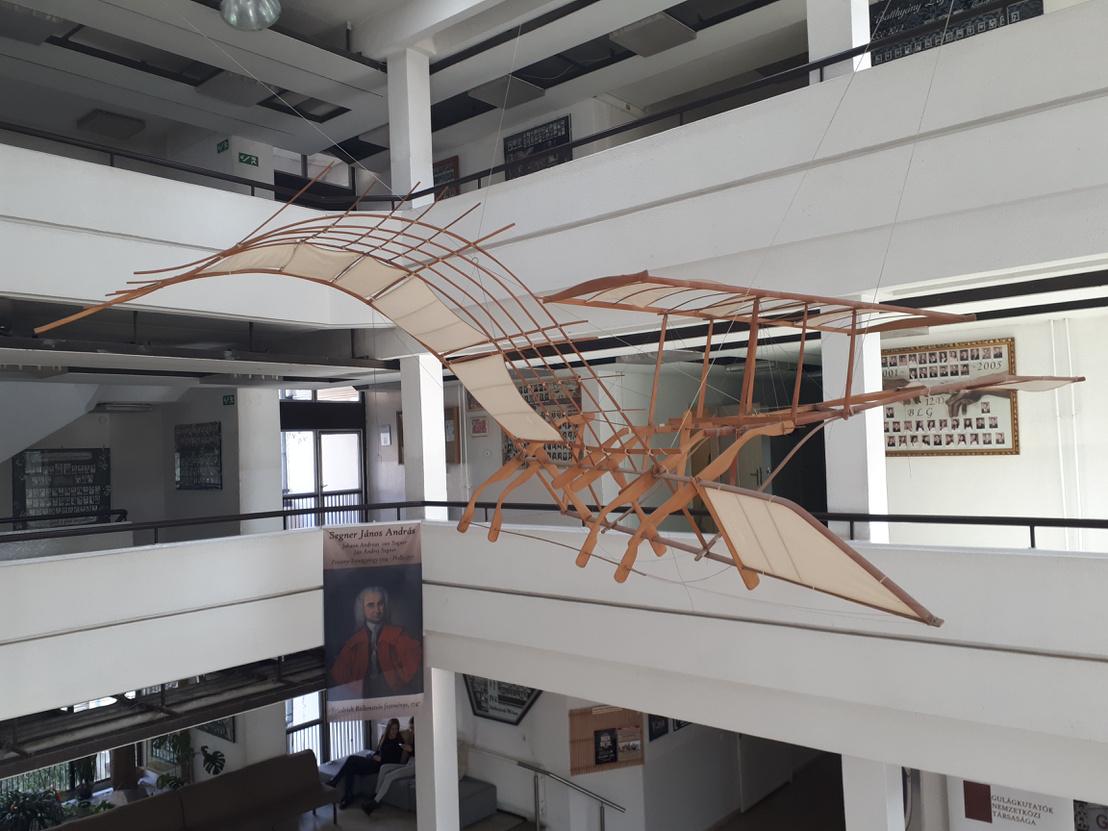 Félig sárkány, félig repülő. Félig szobor, félig installáció. Mindenesetre feldobja az aulát