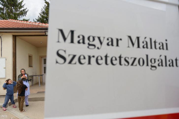 Egy menekült nő gyermekekkel a Magyar Máltai Szeretetszolgálat autója mellett a szabadkai befogadóállomáson
