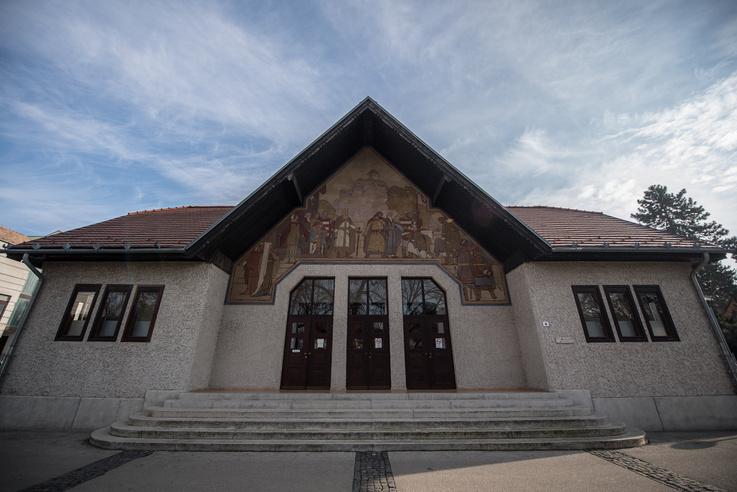 A Medgyaszay Ház főbejárata: ebből az irányból úgy néz ki, mintha egy egészen kis házról lenne szó. A bejárat felett a Bánk bán egyik jelenete látható