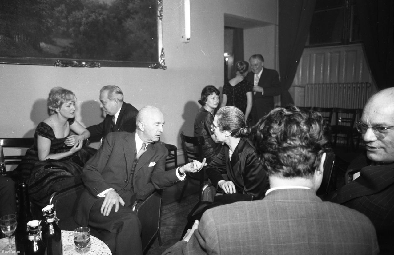 """Szemben Uray Tivadar és Péchy Blanka a Nemzetiből, hátul egy operettasztal Németh Marikával és Feleki Kamillal, a kép jobb szélén pedig a Vígszínház (akkor: Magyar Néphadsereg Színháza) sztárja, állambiztonság beszervezett ügynökeként az egész színházi életről jelentéseket író Szakáts Miklós. Maga választotta a """"Cyránó"""" fedőnevet a szerepálma után, bár általában neki jutott az ellenszenves szerep: Gestapo-ügynök, katonatiszt, vagy éppen kém, int a valóságban is: a magyar III/III. mellett kettős ügynökként a briteket is kiszolgálta – majd 1969-ben disszidált."""