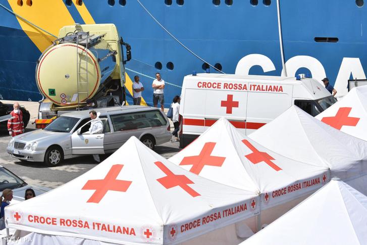 Halottaskocsik és az Olasz Vörökereszt sátrai az EU határvédelmi ügynöksége, a Frontex svéd felségjelű hajója mellett, miután az 650 menekülttel a fedélzetén kikötött a szicíliai Cataniában 2017. július 1-jén.