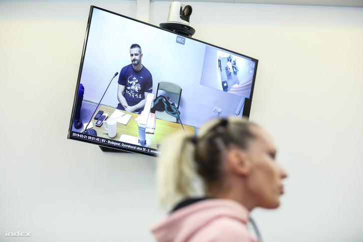 A vádlott a videóközvetítésen, előtérben Pásztor Anna