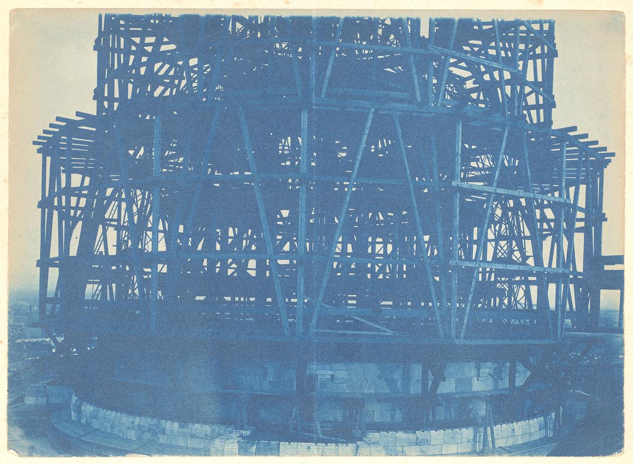 A Szent István Bazilika kupolájának építése, cianotípia, 1889 körül. Az 1850-es évektől az 1950-es évekig használt, az utóbbi években újra felfedezett vas-alapú fotográfiai eljárás jellegzetes színárnyalatú, vegyszeresen könnyen manipulálható pozitív képeket hoz létre a fényérzékeny papíron. Az ismeretlen XIX. századi fotós képe Budapest egyik jellegzetes épületét mutatja építés közben, az archaikus fotótechnika jellegzetes kékes árnyalatába mártva a főváros fölé magasodó bámulatos fa állványzatot.