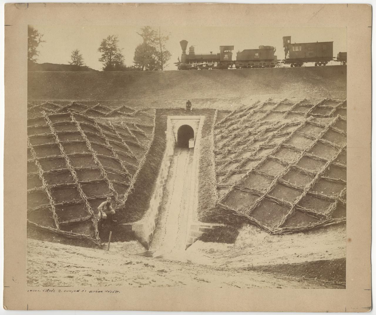 Vasúti töltés Bánffyhunyad és Sztána között, 1869 tájékán – Veress Ferenc (1832-1916) albumin printje. Az erdélyi, nemesi származású Veress a magyar fotótörténet egyik úttörő alakja, 18 évesen már volt saját kamerája, rá pár évre már saját műterme is, és folyamatosan új fényképezőgépekkel, objektívekkel, fotótechnikákkal, fotokémiai eljárásokkal kísérletezett. Élete során több mint ötvenezer portrét készített, de főképp erdélyi tájképeiről, kolozsvári városképeiről vált ismertté. Képeit albumokban mutatta be, mondhatni a fotókönyvek korai feltalálói közé tartozott. Tájfotós tevékenységének fontos részét képezte a vasútvonalak kiépítésének dokumentálása, kora legkorszerűbb közlekedési eszközében a technikai haladás, a társadalmi fejlődés gyorsulásának szimbólumát látta, láttatta.