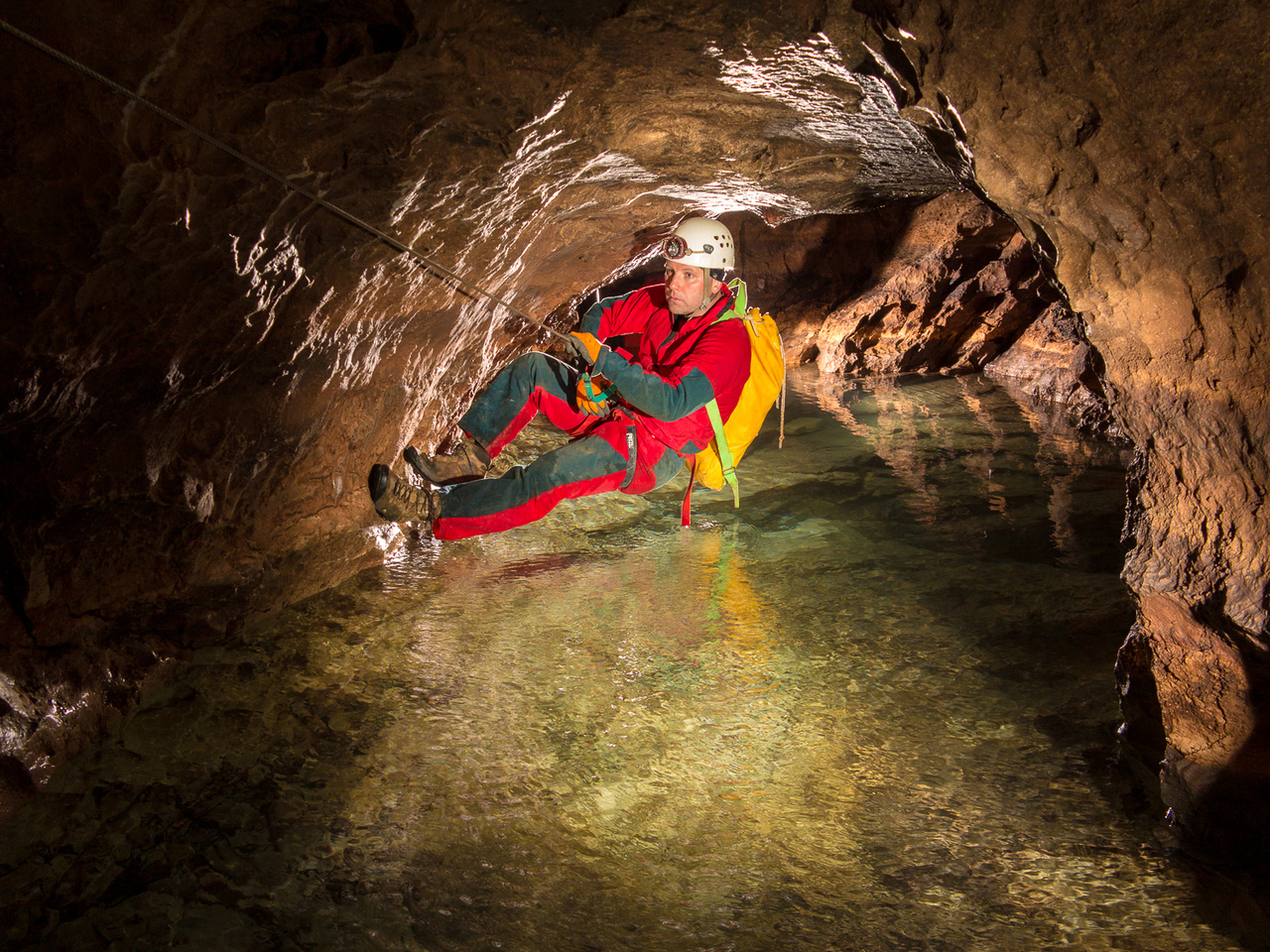 A kötélhidak segítségével közlekednek a barlangkutatók az alpesi Eolo barlangban, hogy a jeges patakok felett szárazon átjutva folytathassák útjukat a hegy gyomrában.