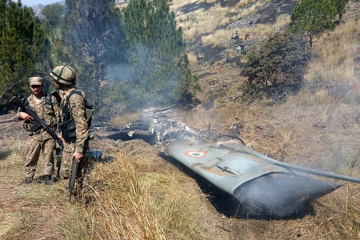 Pakisztáni katonák a lelőtt indiai harci repülőgép roncsánál, a Pakisztán által ellenőrzés alatt tartott Kasmír területén 2019. február 27-én