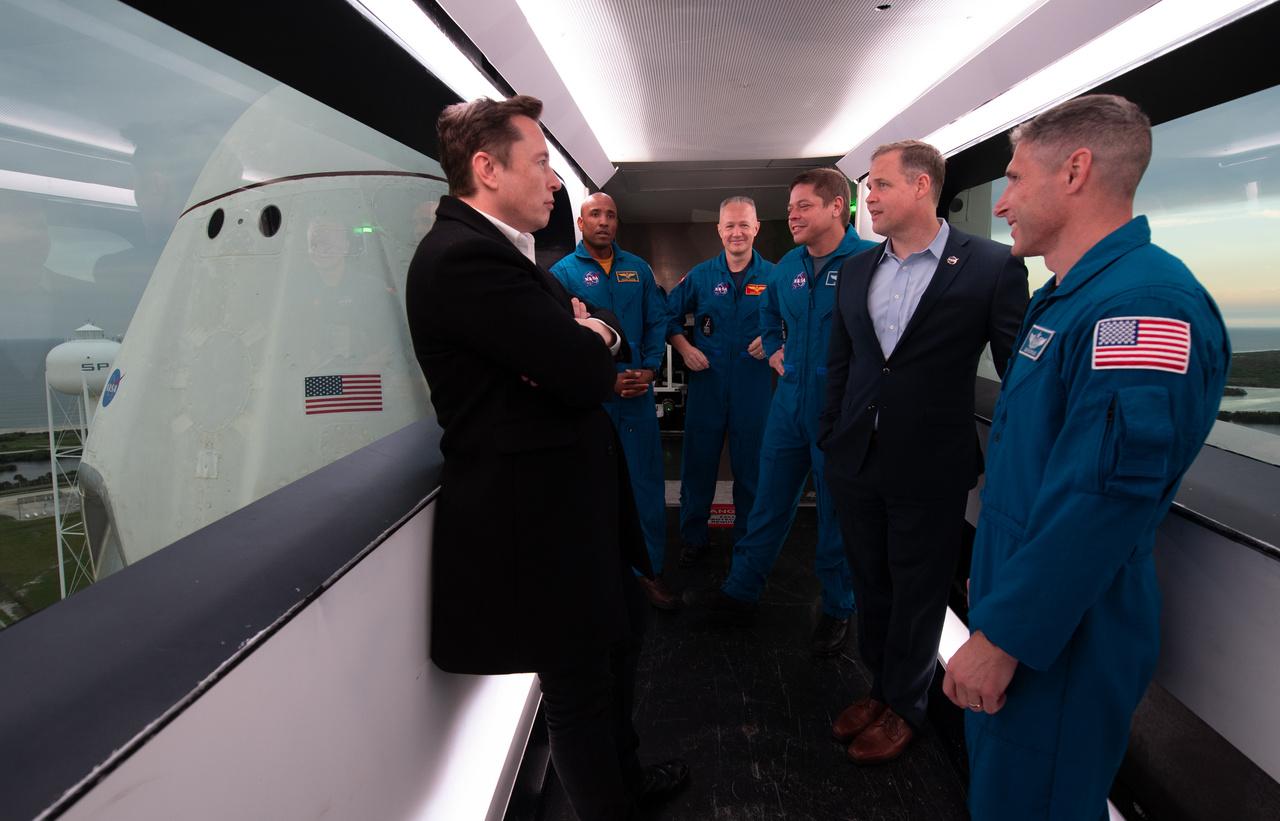 Elon Musk, a SpaceX tulajdonosa, fő tervezője és igazgatója (bal szélen) március 1-jén a NASA igazgatójával, Jim Bridenstine-nal valamint négy NASA-űrhajóssal (Victor Glover, Doug Hurley, Bob Behnken, Mike Hopkins) a startállás karjában egyeztetnek az előttök álló Demo-1 küldetésről.