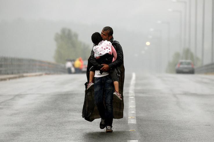 Egy szíriai menekült és kislánya a szakadó esőben a görög-macedón határnál 2015. szeptember 10-én.