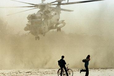 Két albán figyeli az amerikai haditengerészet egyik helikopterének érkezését a tengerparti Durrës városában, 1997 márciusában.