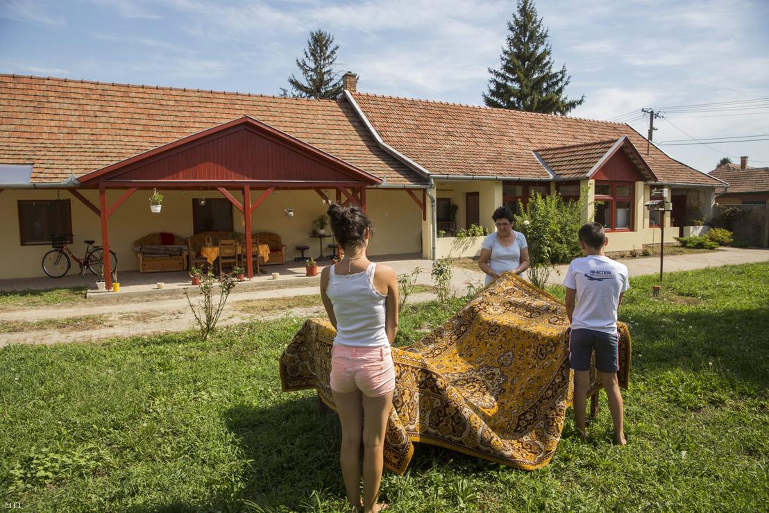 Pintér Istvánné nevelőszülő gyerekekkel pakol az SOS Gyermekfalu egyik házának udvarán 2015. augusztus 11-én, miután megkezdték a gyermekfalu lakóinak átköltöztetését Battonyáról Orosházára.