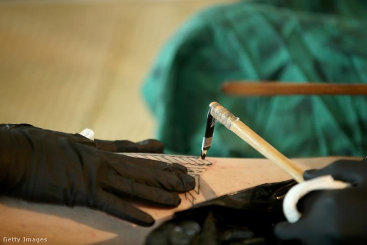 Ennek a kézi tetováló eszköznek csontból készült 2700 évvel ezelőtti változatát találták meg. Tradicionális, kézzel ütött tetoválást készítenek a Maori tetováló fesztiválon 2018. január 27-én, Auckland-ben.