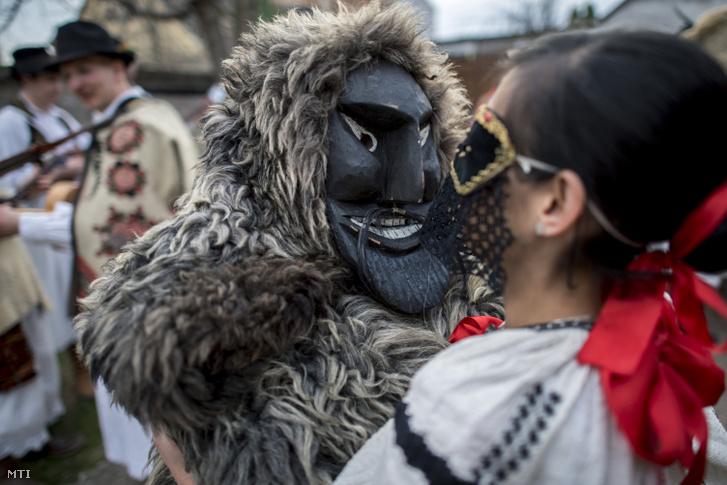 Busó és egy sokác népviseletbe öltözött lány táncol a mohácsi busójárás ötödik napján, március 4-én.
