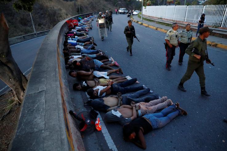Letartóztatott fosztogatók fekszenek az utcán Caracasban 2019. március 10-én