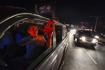 Emberek használják a mobiljukat a Francisco Fajardo főúton, ahol találnak térerőt az áramszünet idején Caracasban 2019. március 9-én