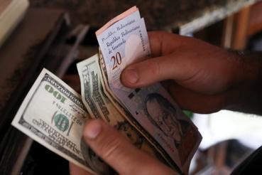 Dollárral és venezuelai bolivar bankjegyekkel fizet egy vásárló a pékségben Caracasban 2019. március 10-én