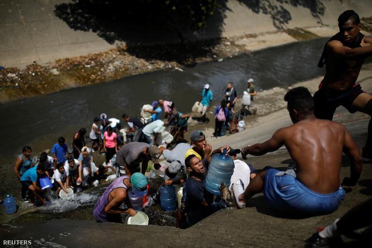 Emberek gyűjtik be a vizet a szennyvízcsatornán keresztül, ami a Guaire folyóba ömlik Caracas-ban 2019. március 11-én
