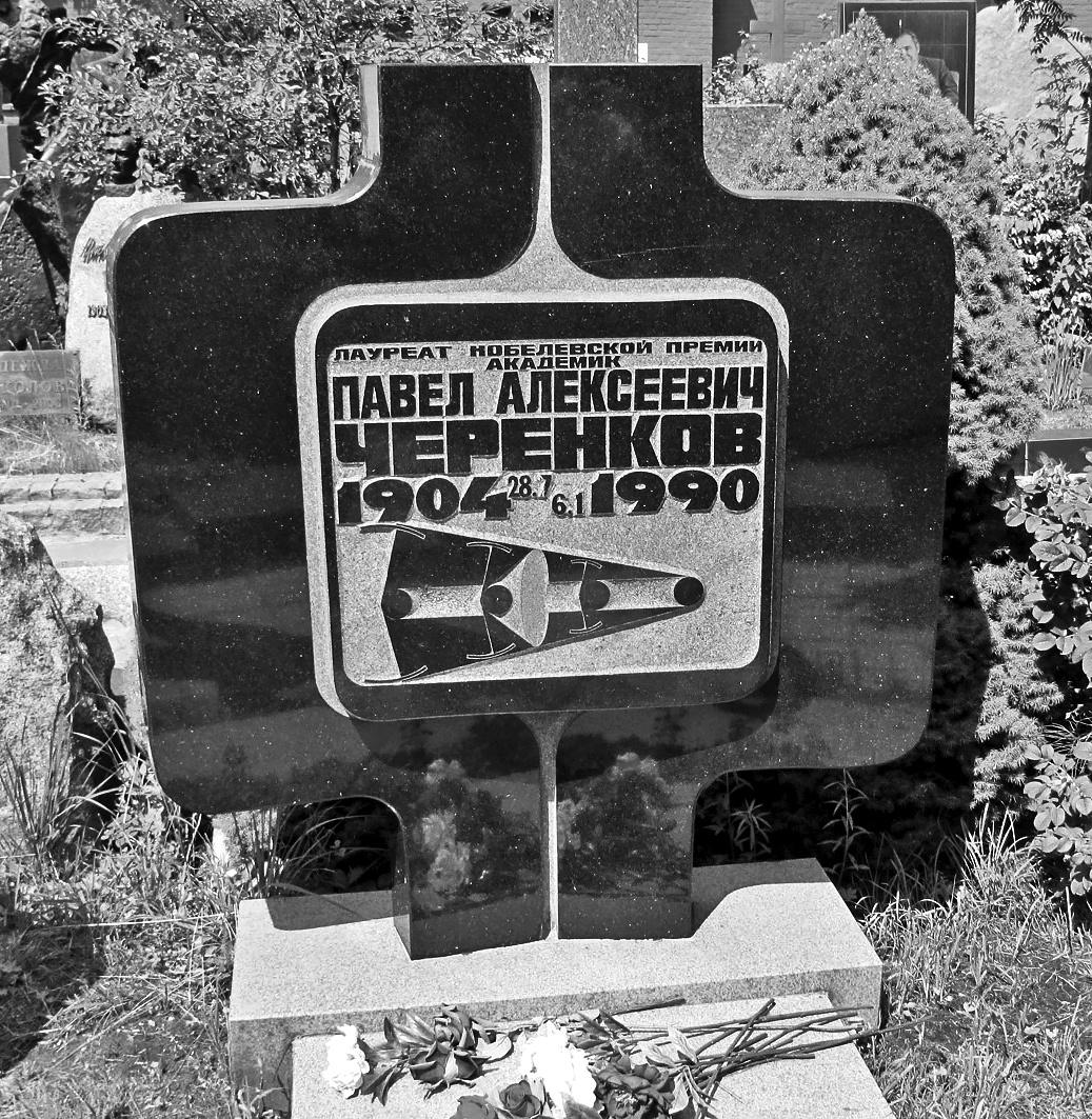 """Pavel Cserenkov síremléke a novogyevicsi temetőben. A  sírkő rajzolata a Nobel-díjas fizikusról elnevezett Cserenkov-effektust, illetve a Cserenkov-sugárzást ábrázolja. A Cserenkov-effektus lényege: ha egy töltött részecske (például egy elektron) egy szigetelőanyagban a közegben érvényes fénysebességnél gyorsabban halad, akkor haladása során kúp alakban elektromágneses sugárzást bocsát ki. Atomreaktorok hűtővizénél figyelhető meg például az effektusnak köszönhető kékes derengés. A sírkőn ez a kúp alak figyelhető meg a balról jobbra haladó """"részecskegolyó"""" mögött."""