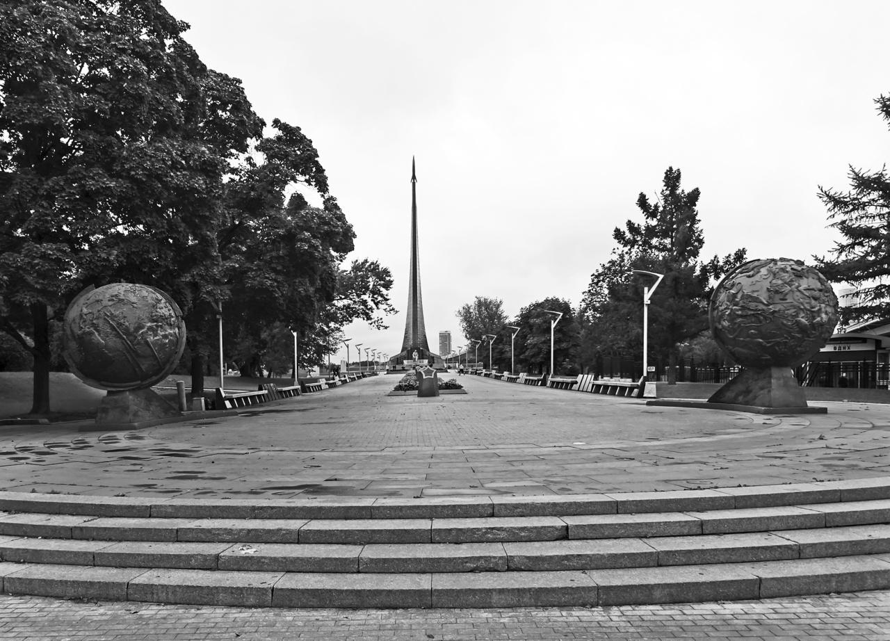 """Moszkva talán legismertebb, a város egyik jelképének számító szobra, a rakétastartot formázó """"A kozmosz meghódítói"""" emlékmű az Űrhajósok sétánya felől nézve. (A sétány elején a Földet és a világegyetemet jelképezi a két gömb.) A 107 méter magas emlékmű titánból készült, 1964-ben állították a szovjet űrprogram kezdeti sikereit ünnepelve."""