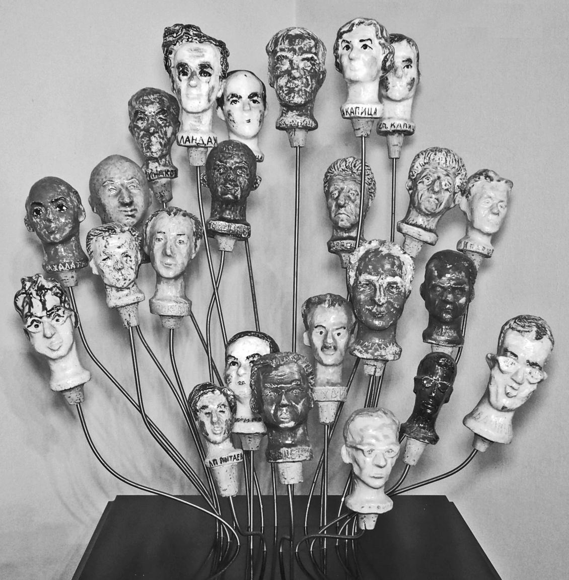A huszonnégy fejű fizikussárkány: Pjotr L. Kapica és legközelebbi munkatársai 1964-ben készült majolikadugókon. Kapica (legfelül a középső fej az övé) a mágnesesség tanulmányozásában szerzett elévülhetetlen érdemeket.