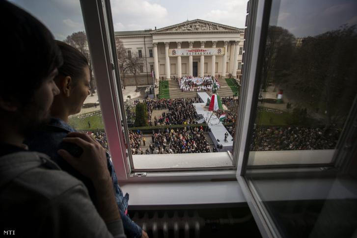 Fiatalok egy lakás ablakából Orbán Viktor miniszterelnök beszédét hallgatják az 1848-49-es forradalom és szabadságharc 167. évfordulója alkalmából rendezett állami ünnepségen Budapesten, a Múzeumkertben 2015. március 15-én.