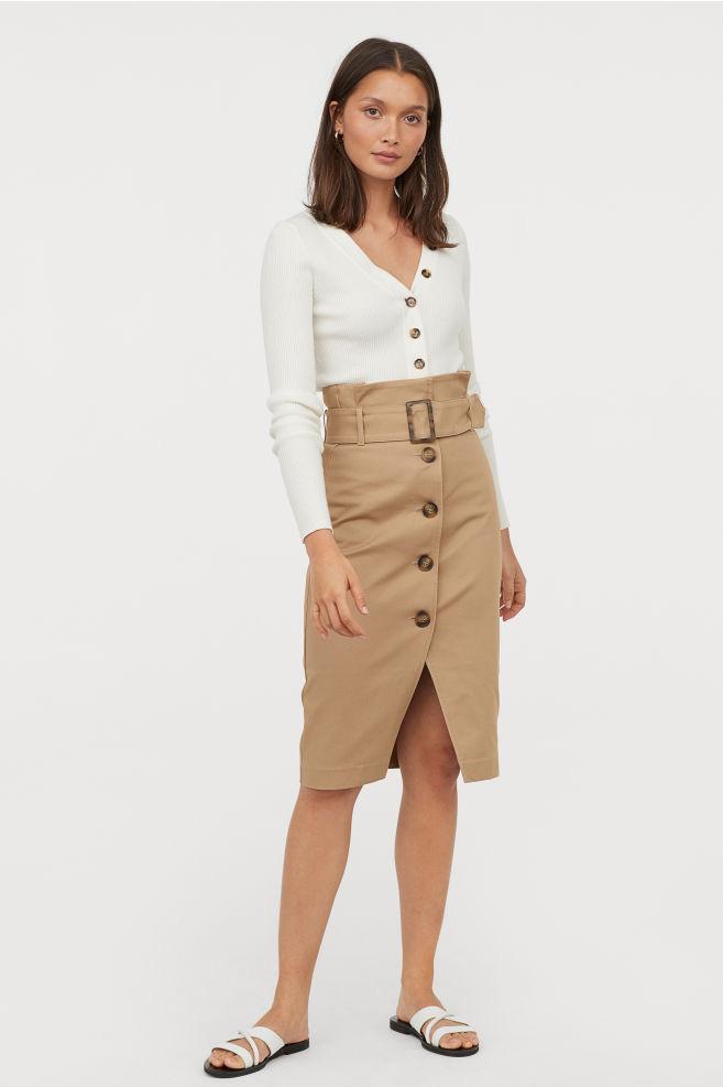 A H&M magasított derekú, öves, elöl gombos szoknyája nemcsak extra nőies, de szépen formál is. Eltakarja a hasat, vékonyabbnak láttatja a derekat, és nyújtja a lábakat. 8995 forintért veheted meg.