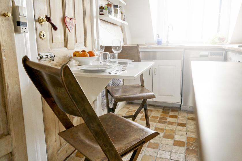 A helyhiányt könnyű orvosolni, ha összecsukható asztalt és széket használ az ember. Ezeket étkezés után el lehet tenni. Az ajtóhoz illő fehér, kihajtható asztal és a faszékek így is romantikus hangulatot teremtenek két főnek.
