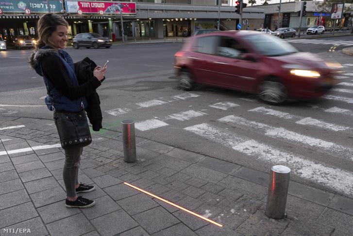 Izraeli nő nézi a telefonját, miközben pirosat jelez a földbe épített gyalogos lámpa egy tel-avivi kereszteződésben