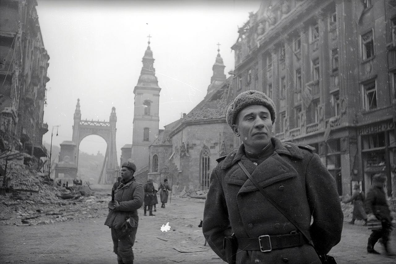 Még áll a Dunába robbantott régi Erzsébet-híd hídfője, a Belvárosi templom tetején kisebb lyuk, balra a romos Klotild-palota kövei. A város épületeinek háromnegyede megsérült vagy lakhatatlanná vált a háborúban.