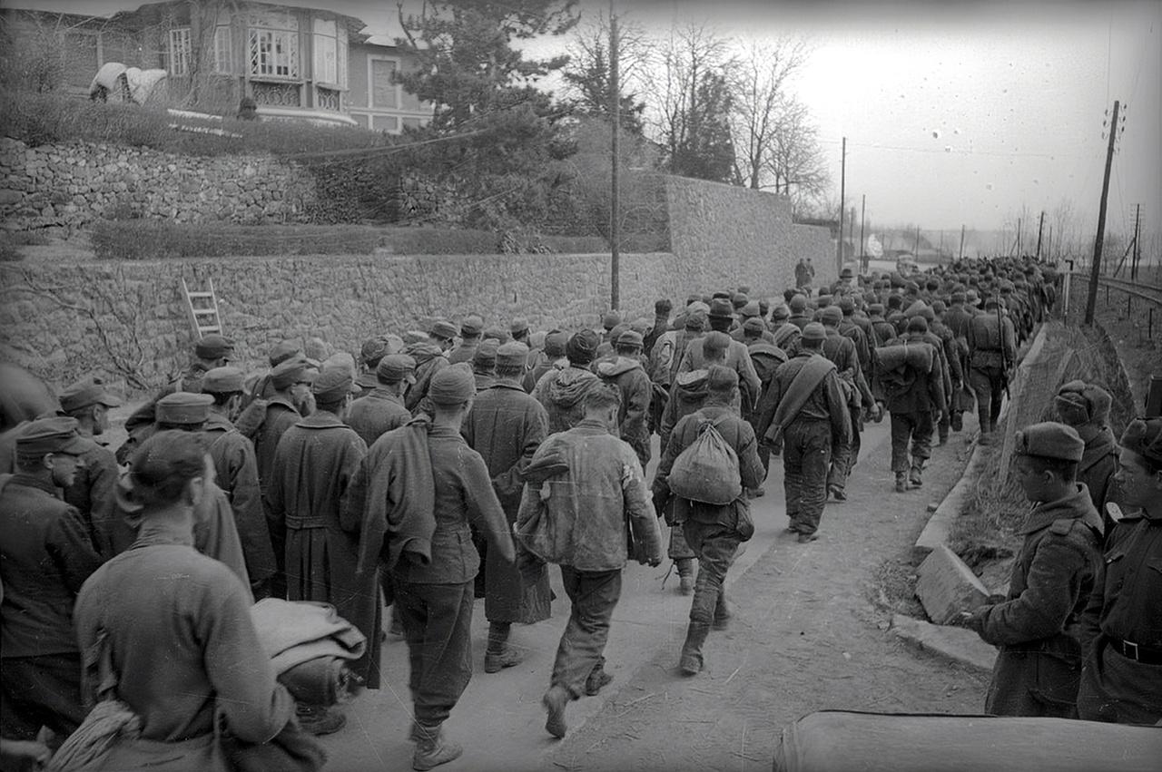 A Balatonalmádi villasor előtt, a főúton vonul lerongyolódott magyar katonák, valószínűleg úton a hadifogságba.