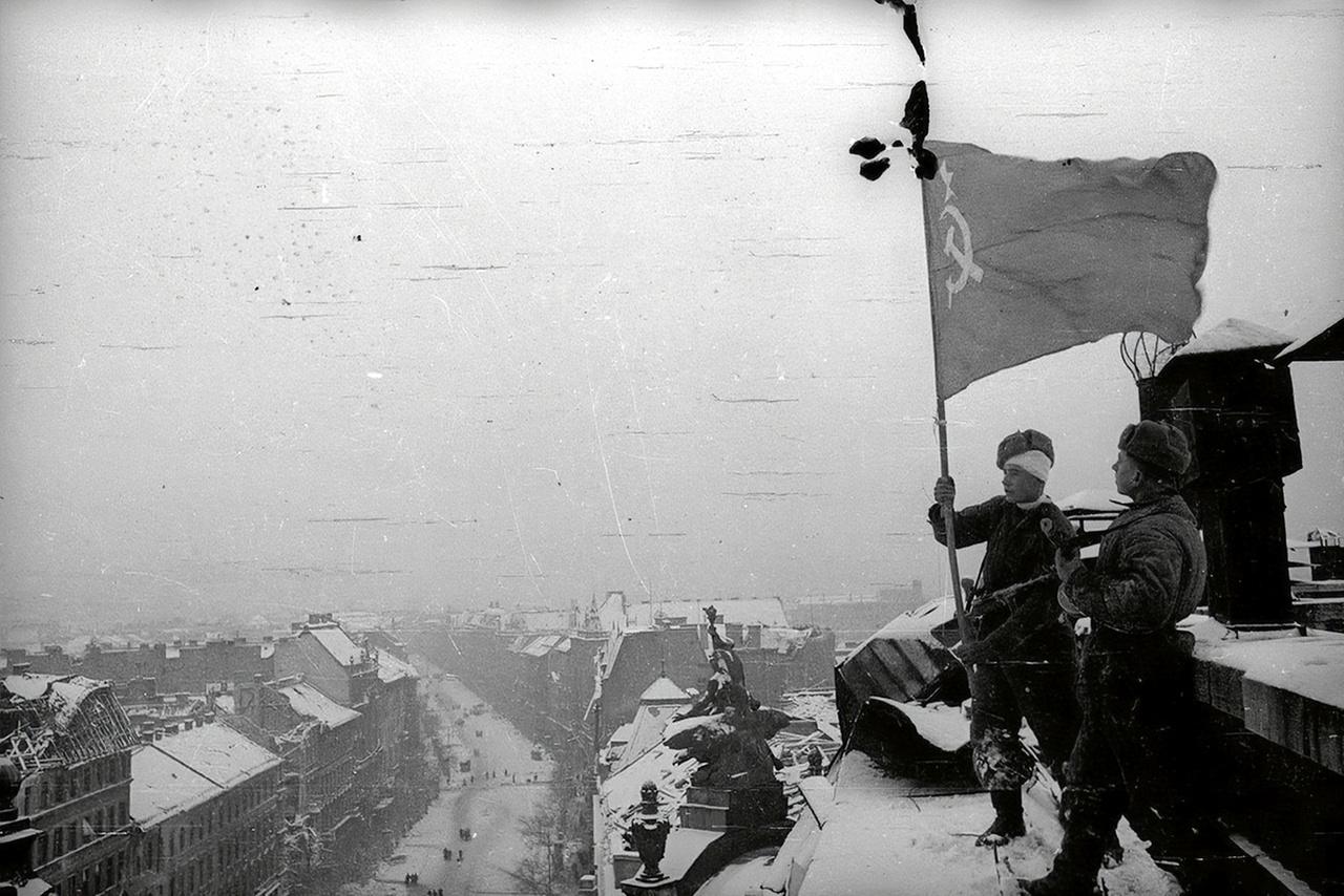 Szovjet vörös zászló lobog a pesti New York palota tetején. A kép erősen emlékeztet Haldej leghíresebb fotójára, a Berlin bevételét a Reichstag tetején szovjet zászlót kitűző győzedelmes vörös katonával hitelesítő propagandaképre. Az a kép Haldej sok más felvételéhez hasonlóan erősen manipulált: a valós események után egy nappal a fénykép kedvéért játszatta újra a történteket, a fotós maga varrta hozzá a zászlót, a montírozások után pedig kiretusált a katona karjáról egy második karórát, hogy mégse legyen ott a zabrálások egyértelmű jele. A válogatásunkban látható képek elsősorban szintén a propagandáról szóltak. Többségüket feltehetően valóban Haldej készítette, de biztosra ezt nem lehet venni mindegyik esetben.