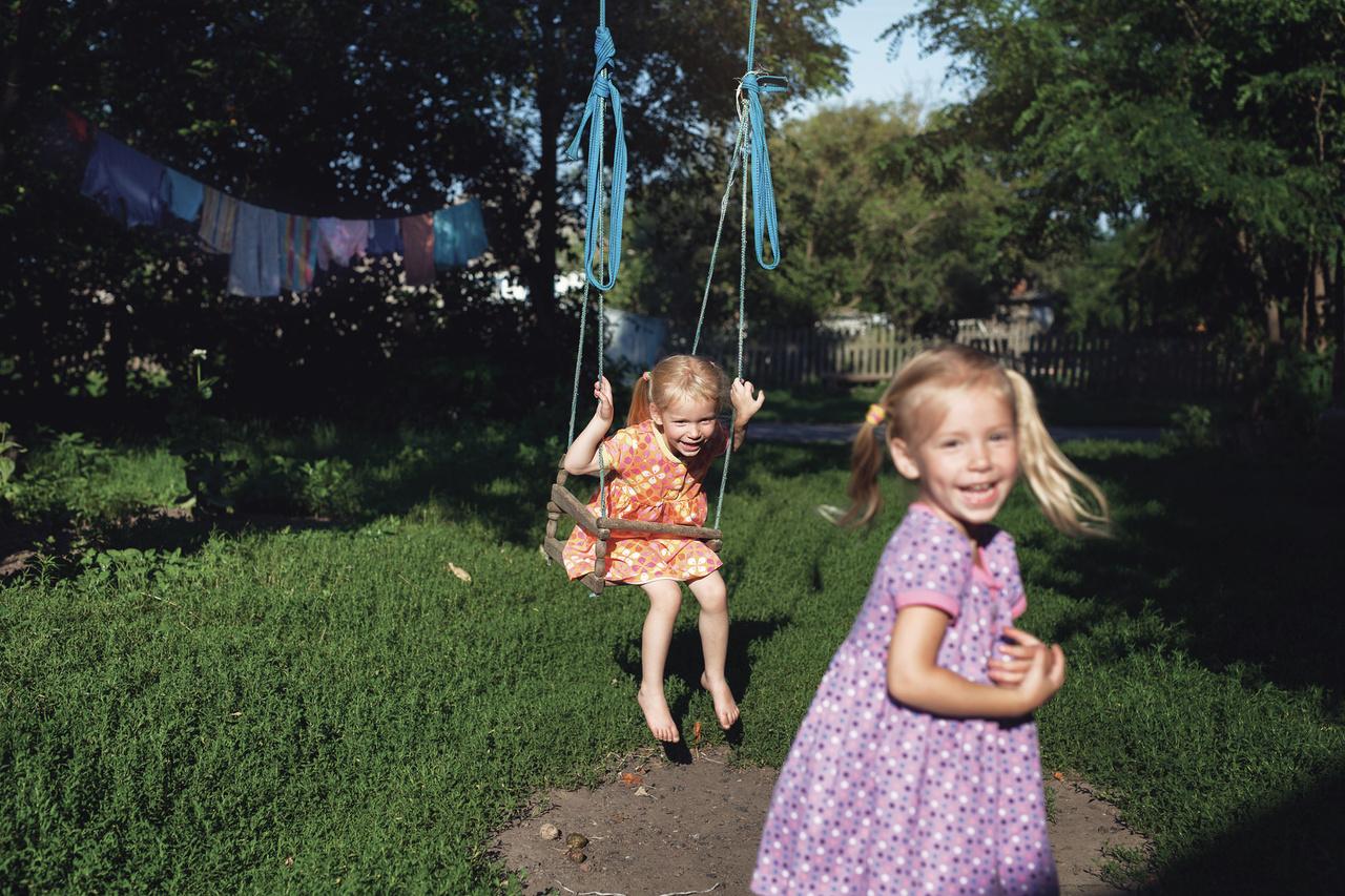 Mezítlábas kislányok játszanak egy ukrajnai falu egyik udvarán.