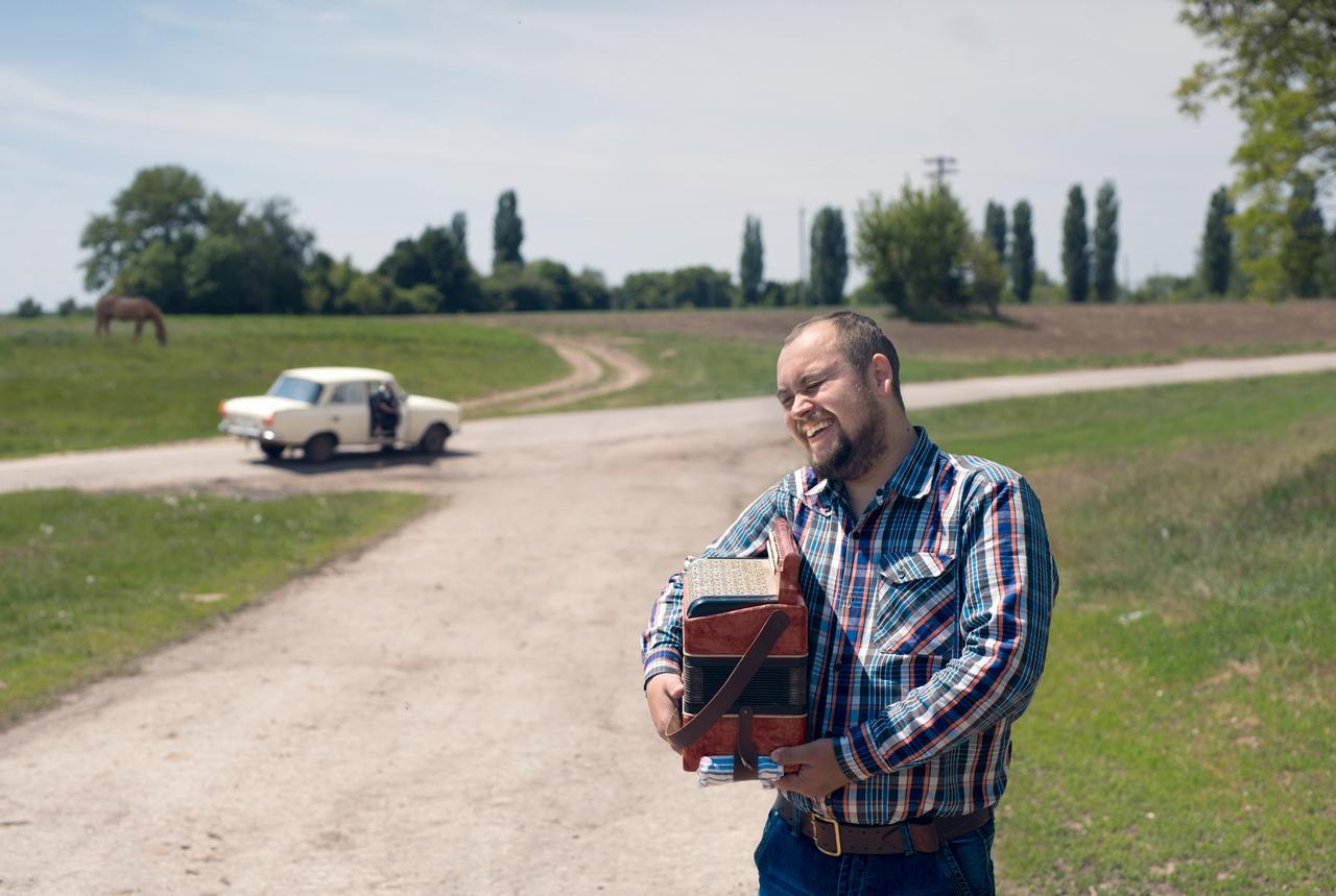 """A csernihivi Olekszej édesanyja Csernobiltól három kilométerre született, és az 1986-os katasztrófa napján is a földeken dolgozott. """"Nem sokkal később buszok érkeztek a faluba és mindenkit felszállítottak, azzal az instrukcióval, hogy két heti ruhát vigyenek magukkal. Kerteket, megművelt földeket, állatokat, a temetőben nyugvó családtagjaikat hátrahagyva elindultak a két hetes távollétre, ami azóta is tart, soha többé nem fognak visszatérni. Minden elköltöztetett falunak kijelöltek egy befogadó falut, minden ház kapott egy új családot. Az addig gazdag földekkel, sok állattal rendelkező földművesek az éhezés miatt vödrökkel jártak krumpliért kopogtatni házról-házra. Ebből a kényszerített betelepítésből komoly konfliktusok támadtak a helyiek és a jövevények között. Később a falu határában épített nekik az állam házakat, és ma is ott élnek. Olekszej egy ilyen kényszerült helyzet szülöttje; édesanyja betelepült, édesapja már a fogadó faluból származott. Az ott szövődő szerelemből született 1989-ben."""""""