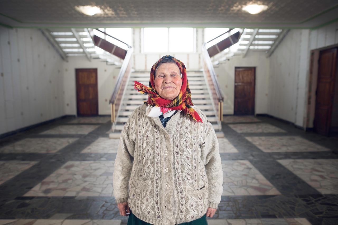 """Asszony a kultúrházban. """"A negyvenes-ötvenes években minden faluban nagy erővel elkezdtek épülni a kultúrházak. Hatalmas színháztermekkel, vetítőgépekkel, könyvtárral, működő kórussal, mindennel, amire a kor szovjet emberének kulturálisan szüksége lehetett a központi vezetés szerint. Mára a falvak elnéptelenedésének köszönhetően általános, hogy a termeket már csak pár tucat özvegyasszony használja, állapotuk gyakran életveszélyes, de legalábbis alig karbantartott."""""""