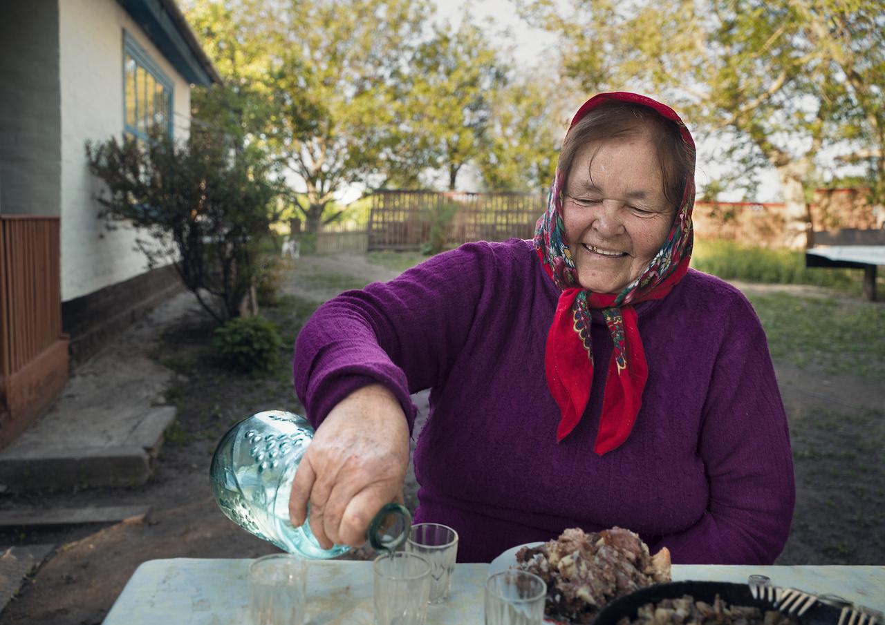 """A Poltava területről származó Nina Alekszejivna derűsen itatja vendégeit az udvarán. """"Két testvérével együtt szüleiket a háború alatt elveszítették. Emiatt a három árvát a falu nevelte fel. A három nővér gyönyörűen énekelt, és azzal hálálták meg a falusiak segítségét, hogy a közösség különböző ünnepein, vagy csak akár házról-házra járásként mindenkinek énekeltek. Nina mindkét testvére meghalt azóta, de jókedve és csodálatosan csengő hangja miatt az egész faluban köztiszteletnek örvend."""""""