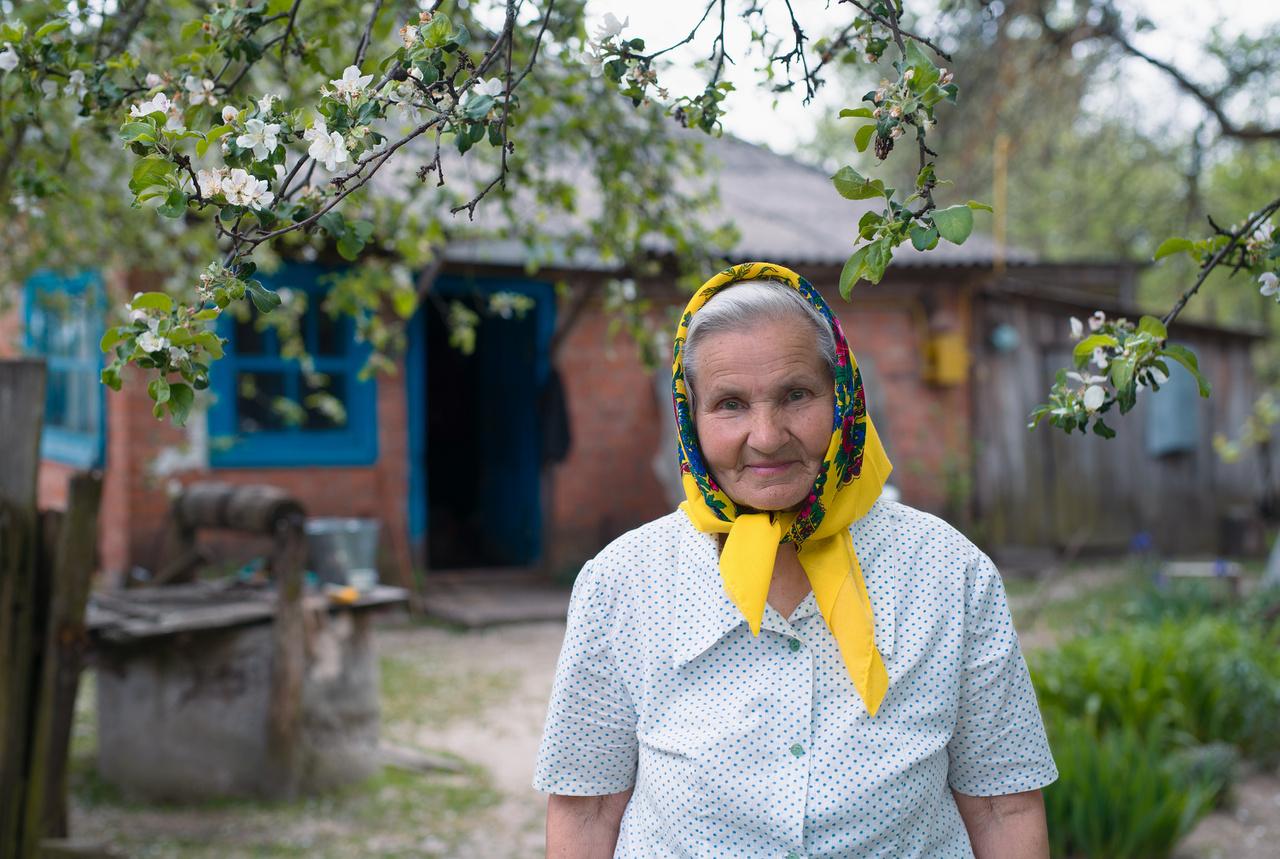 """A 81 éves Okszána Deniszovna a cserhinyivi háza előtt. Lánya autóbalesetben halt meg, ami miatt az idős nő hat éven át nem nézett tévét, nem hallgatott rádiót, nem ment vendégségbe és tíz évig nem énekelt. """"Az egyik legmelegebb szívű vendéglátónk. Egyik este álmában eljött hozzá a leánya, és megkérte, hogy énekelje el azt a hosszú éneket, amikor madár testben visszaszáll a lány a szülői házhoz. Hajnalban kiment cseresznyefája alá és újra énekelni kezdett. Hosszú balladáit azóta lányának énekli."""""""