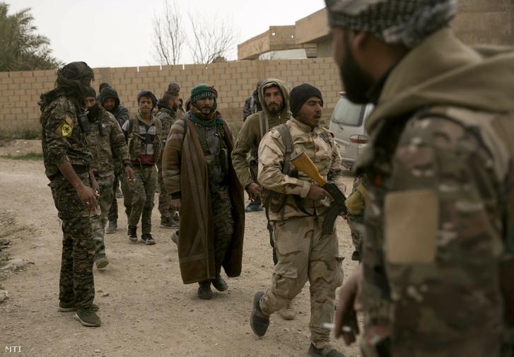 2019. március 14-i kép az amerikai támogatású Szíriai Demokratikus Erők (SDF) fegyvereseiről az Iszlám Állam dzsihadista szervezet utolsó szíriai zárványa, a keleti Deir-ez-Zór tartományban lévő Baghúz határában. A város felszabadításáért harcoló kurd-arab milícia szerint több mint 60 ezer ember hagyta el a várost az offenzíva január 9-i kezdete óta. Az SDF szerint 29 ezer 600 ember adta meg magát, köztük 5 ezer fegyveres, a többiek a dzsihadisták családtagjai. További 34 ezer civilt az utóbbi pár hétben menekítettek ki a városból.