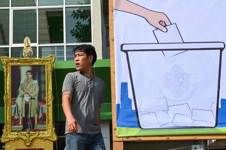 Férfi sétál el a thaiföldi király Maha Vajiralongkorn képe és egy szavazási plakát előtt 2019. március 23-án
