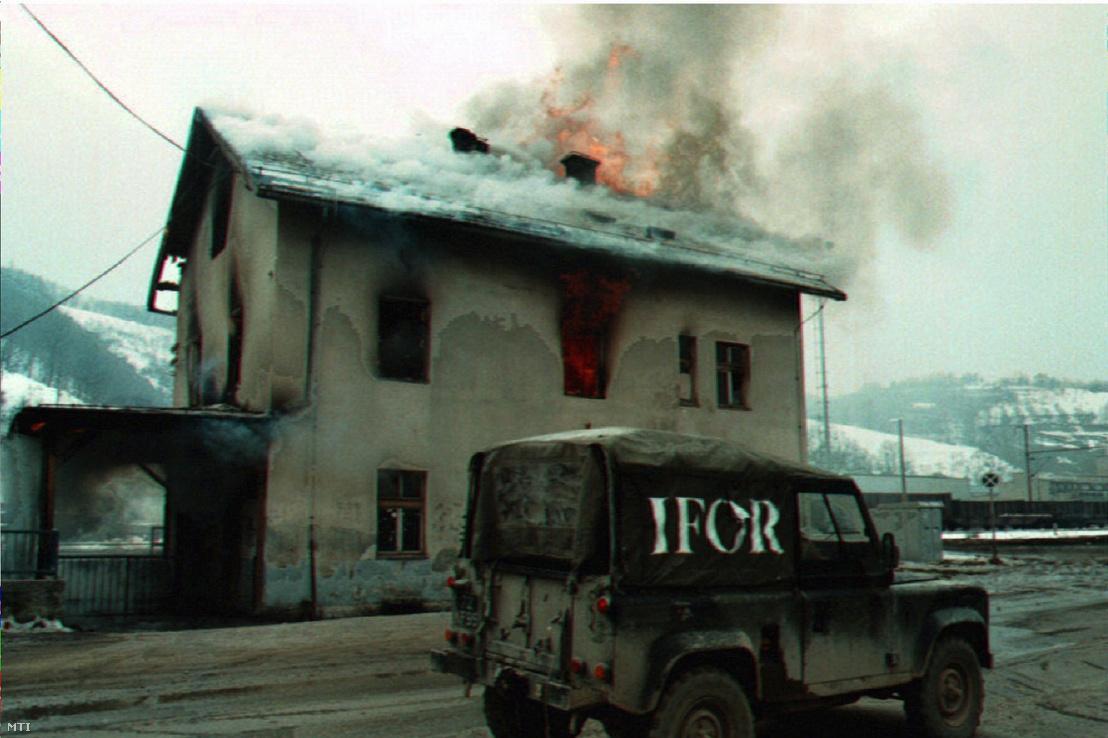 A boszniai NATO -békefenntartók egyik terepjárója elhalad egy lángokban álló ház mellett Szarajevó egyik szerb negyedében, Ilidzában 1996. március 10-én. A szerb uralom alól két nap múlva a muzulmán-horvát föderáció fennhatósága alá kerülő Ilidza szerb lakóinak túlnyomó többsége végleg elköltözik a negyedből, és közülük sokan az eddigi otthonukat is felgyújtják, hogy ne kerüljön a muzulmánok kezére.