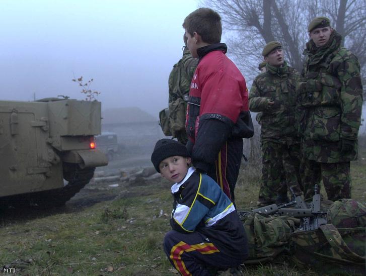 Albán gyerek áll brit KFOR katonák mellett, akik a dél-kelet koszovói, szerb-macedón határ közelében levő Shurdanban járőröznek 2000. december 19-én. A feszültség egyre növekszik az albán fegyveresek és Szerbia déli határán állomásozó rendőrség között. Vojislav Kostunica szerb elnök kijelentette december 19-i beszédében, hogy a NATO békefenntartó erői nem tudják megállítani az egyre szaporodó erőszakos cselekményeket Koszovóban.