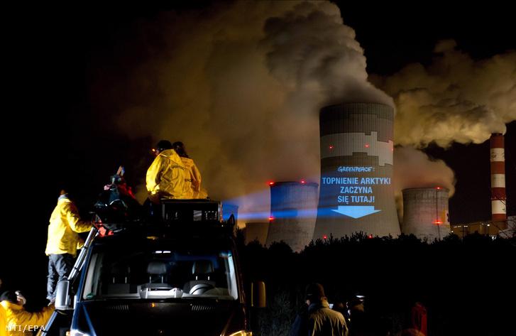 A sarkvidék olvadása itt kezdődik jelentésű feliratot vetítenek a Greenpeace nemzetközi környezetvédő szervezet aktivistái a Lengyelország középső részén fekvő Belchatów erőművének egyik hűtőtornyára 2013. november 9-én.