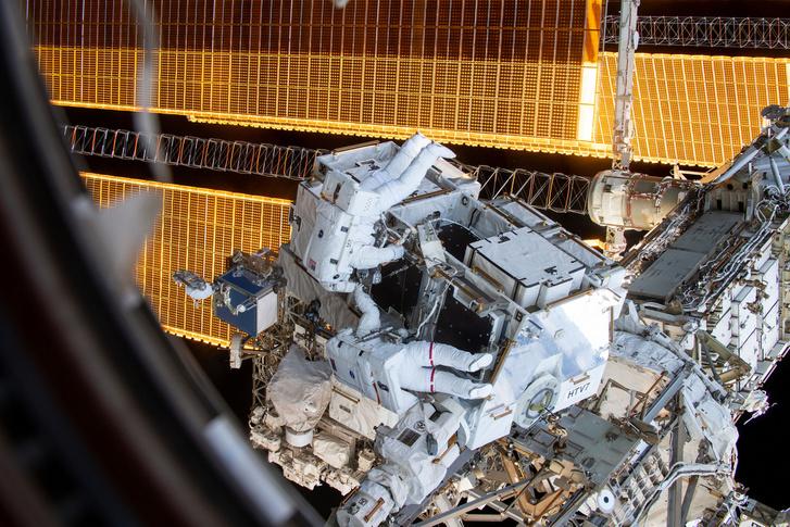Nick Hague, csíkok nélküli ruhában és Anne McClain, vörös csíkkal dolgoznak az ISS energia tároló kapacitás növelésén 2019. március 22-én