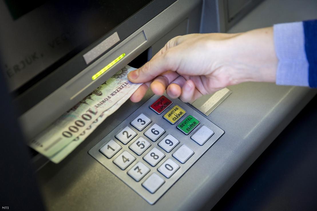 Bankjegyeket vesz ki egy pénzkiadó automatából (ATM) egy ügyfél