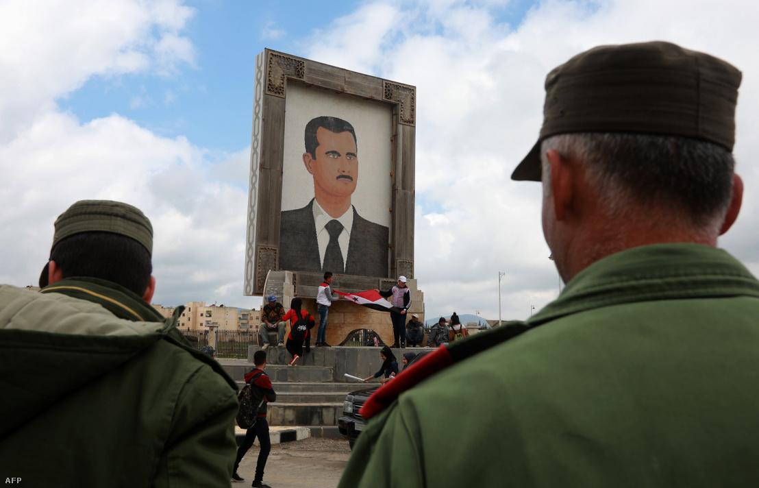 Szíriai tüntetők tartanak zászlót Aszad portréja alatt Quneitra városában, miután az Egyesült Államok elismerte Izrael fennhatóságát a Golán-fennsíkon 2019. március 26-án