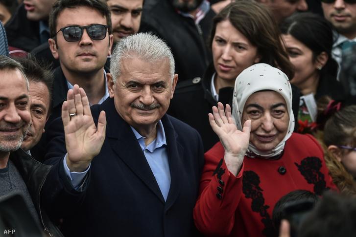 Binali Yildirim (balra), az AKP isztambuli polgármester jelöltje és felesége hagyják el a szavazóhelyiséget Isztambulban 2019. március 31-én
