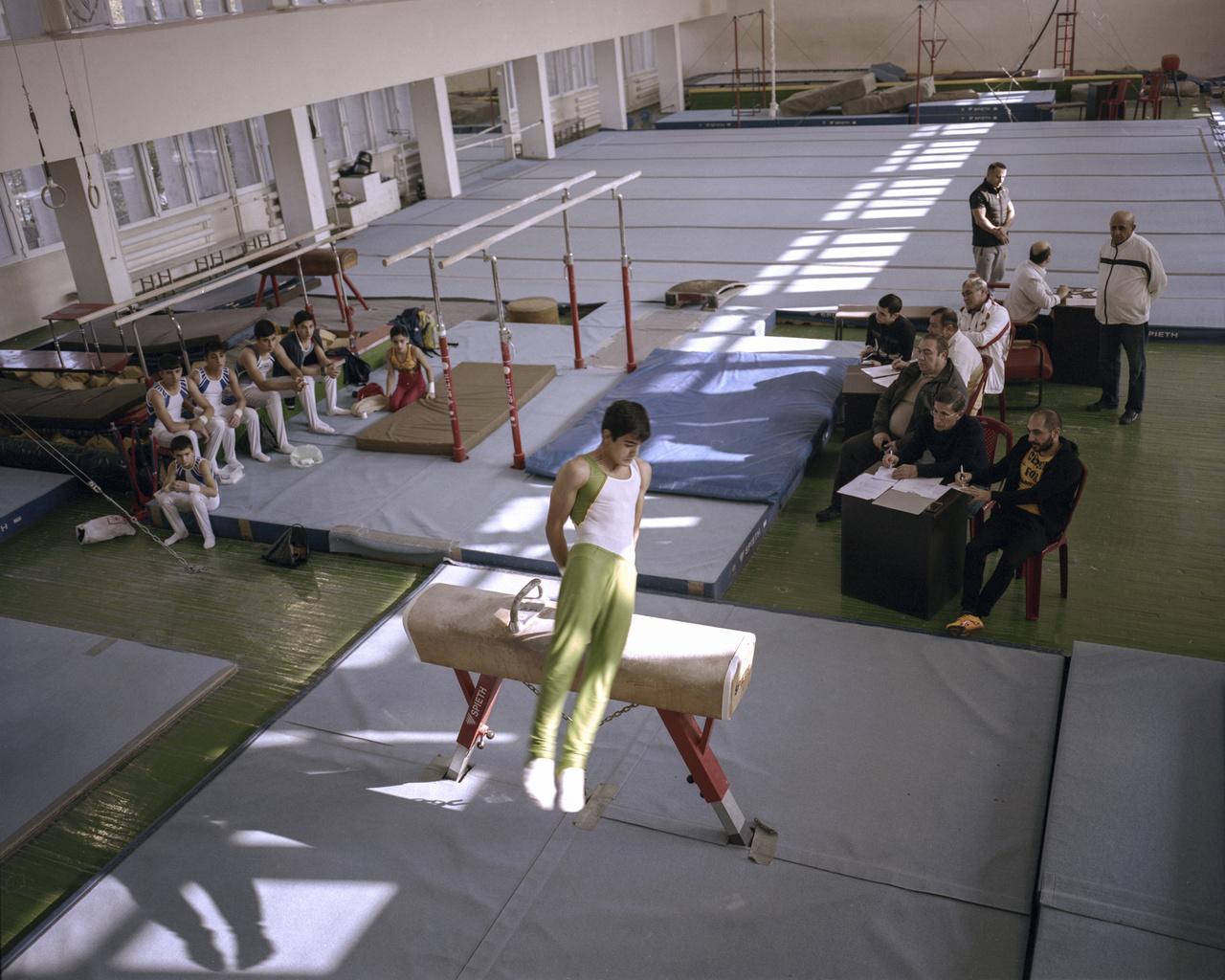 """Bár van egy-két jobb csarnok, mint a kétszeres olimpiai bajnok tornász Albert Azarjan terme, de nem ez az általános. A fűtetlen, bevilágítatlan, omló vakolatú és padló nélkül termek megszokottak, évtizedek óta rohadnak a sportlétesítmények, amelyek még a szovjet időkből maradtak meg. A fotós azzal is találkozott, hogy tornászgyerekek saját maguk varrták a szőnyegeket edzésen. """"Voltam egy vívóedzésen, ahol folyamatosan cserélgették a felszerelést. A gyerekeken lógott a felnőttekre szánt vívóruha."""""""