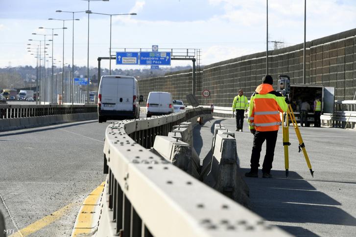 Munkások az M0-s autóút déli szakaszán, az M6-os kihajtójánál 2019. március 5-én. Április elejétől megkezdődik az M0 autóút déli szektorának felújítása, az 1-es főút és az M5-ös sztráda közötti szakaszon új forgalmi rend lép életbe.