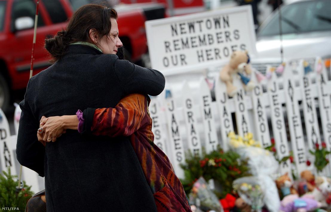 """Gyászoló nők ölelik egymást a tragédia gyerekáldozatainak nevével teleírt kerítés előtt a Connecticut állambeli Newtownban 2012. december 21-én. Egy héttel korábban a húsz éves Adam Lanza agyonlőtt 26 embert, köztük 20 kisgyereket a newtoni Sandy Hook általános iskolában. A táblán olvasható felirat jelentése: """"Newtown emlékszik a hőseinkre""""."""
