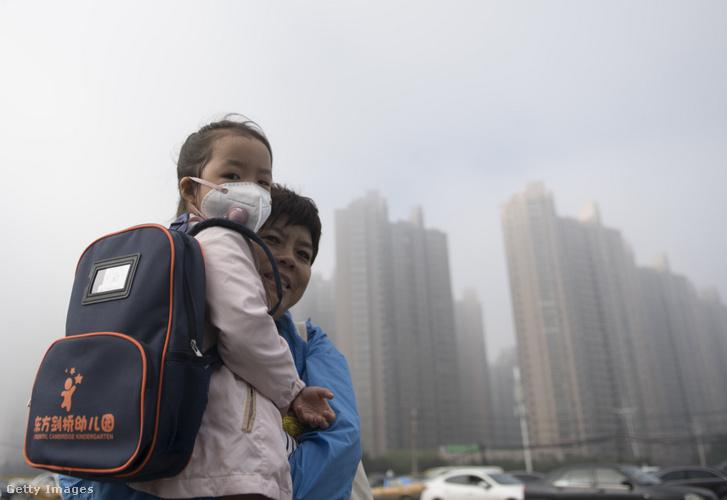 Kínai nő tartja gyermekét a szmogos Harbinban 2018. szeptember 14-én