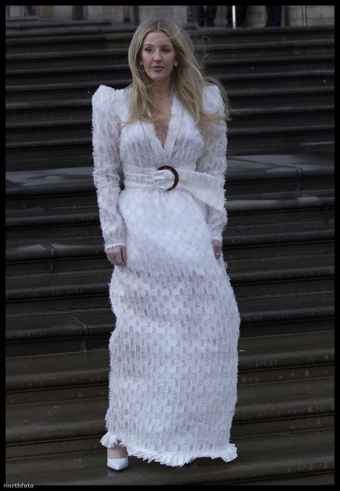 Ő Ellie Goulding énekesnő fehérben, hatalmas vállakkal, hatalmas övvel, hatalmas szélben.