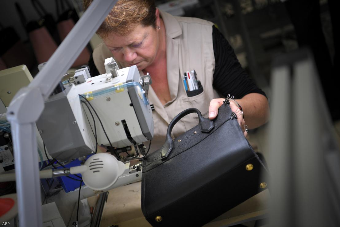 Egy francia varrónő dolgozik Louis Vuitton bőrtáskán Juilley városában 2018. október 12-én